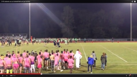 Students tackled after rushing football field (Video)