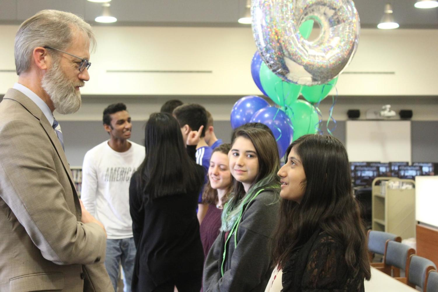 Sriya Kosaraju, sophomore, talks with Superintendent Dr. Eric Knost as he congratulates her on her perfect ACT score. Kosaraju was one of nine students who received a perfect score of 36 on her ACT.